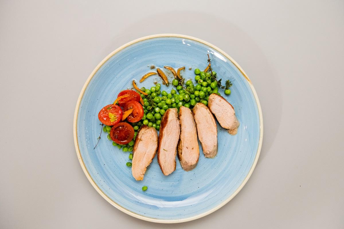 Muschiulet de porc cu mazare verde sotata si rosii cherry marinate